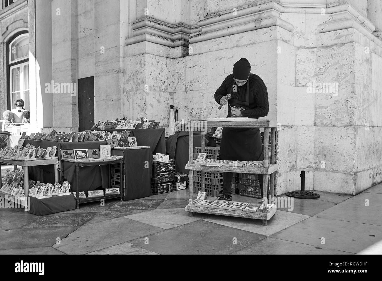 Man carving tiles in Comércio Plaza, Lisbon, Portugal - Stock Image