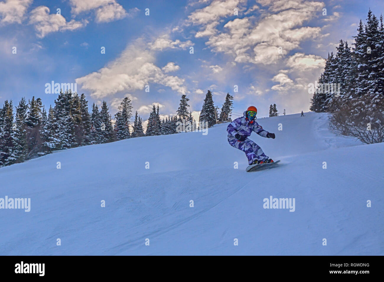 Young man snowboarder running down the slope in Karakol mountains Stock Photo