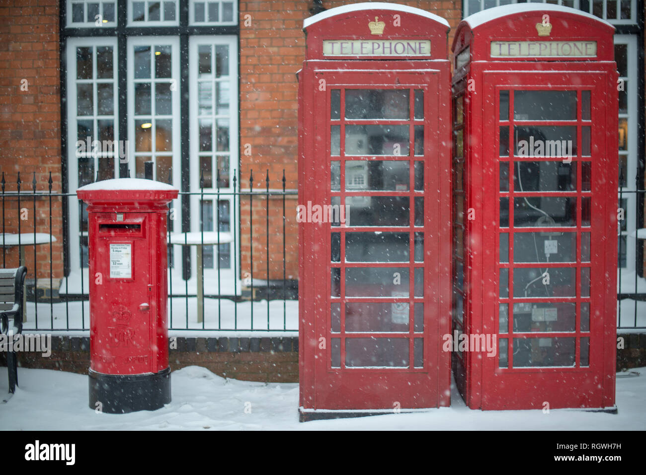 typical red post box and telephone kiosk on UK street during blizzard with snow on top - Stock Image