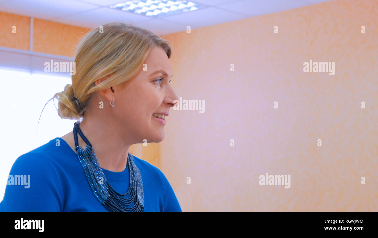 Portrait of professional woman designer, tailor talking with colleague at atelier, studio - Stock Image
