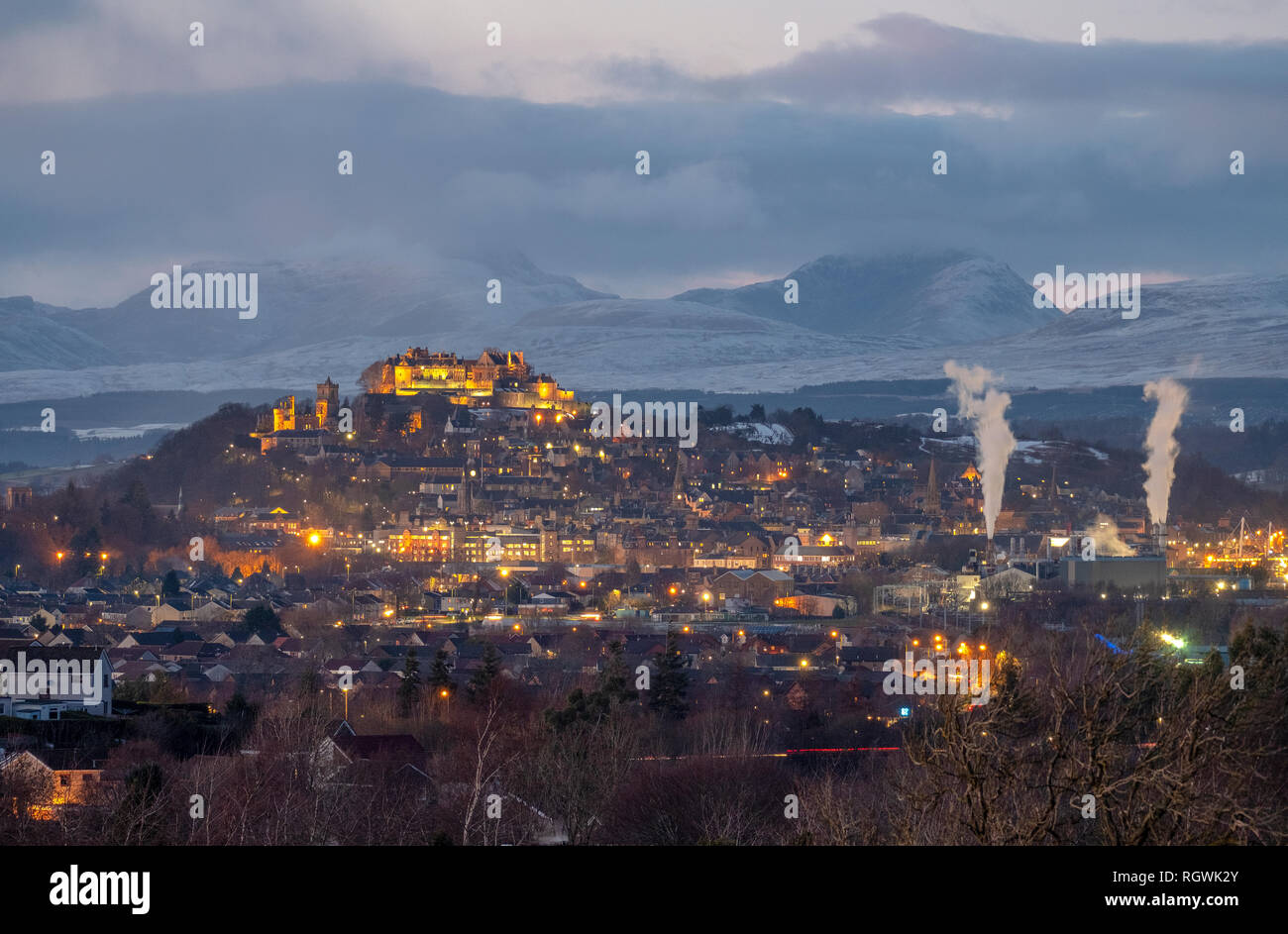 Stirling Castle and town of Stirling at dusk with the snow covered mountain (Stuc a Chroin ) in distance - Stock Image