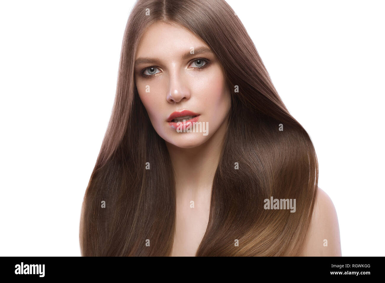 Beautiful brown-haired girl with a perfectly smooth hair, and classic make-up. Beauty face. - Stock Image