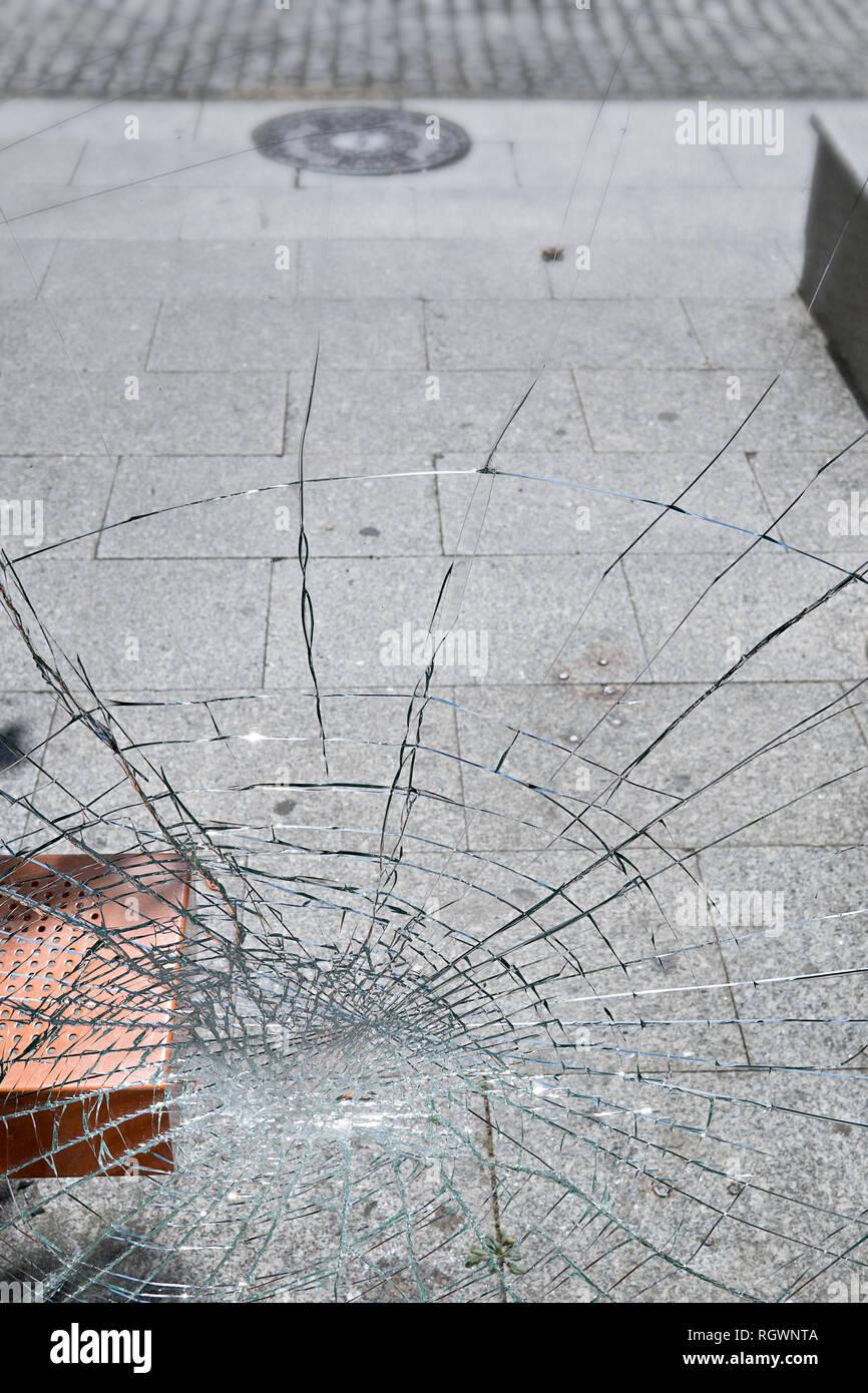 Vandalism concept. Damaged glass at bus stop shelter. Social problems - Stock Image