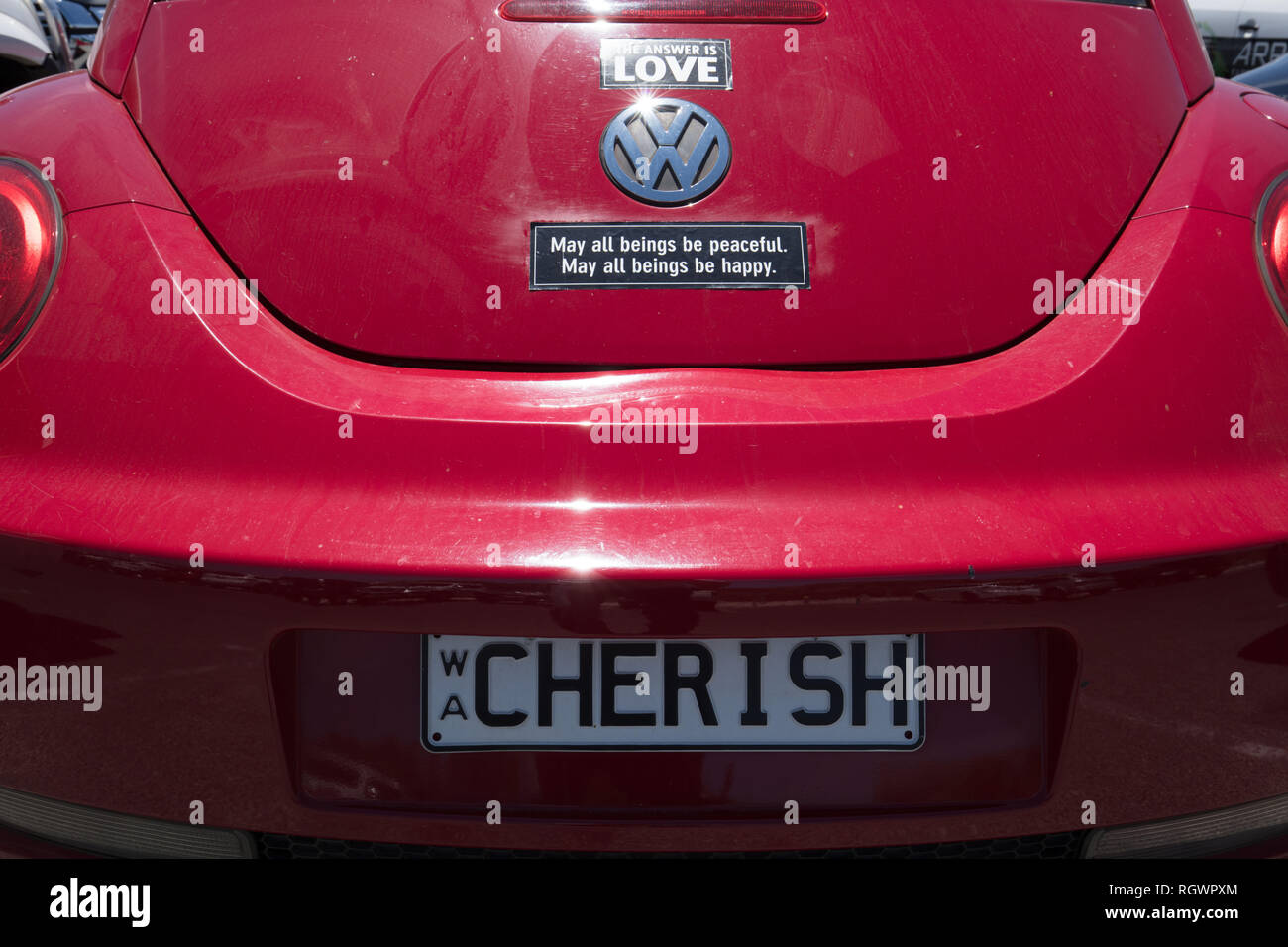 Private Number Plate ' cherish ' and sign stickers of love, peace and happiness on a red Volkswagen Beetle, parked in Whitfords Beach, Perth, Western - Stock Image