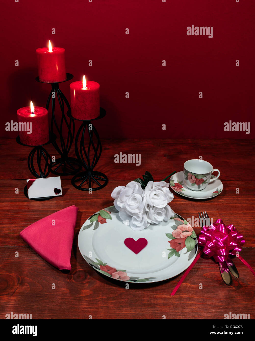 Floral pattern fine china dinnerware with matching plate, cup and saucer. bouquet of white roses, pink napkin, silverware, red candles and card Stock Photo