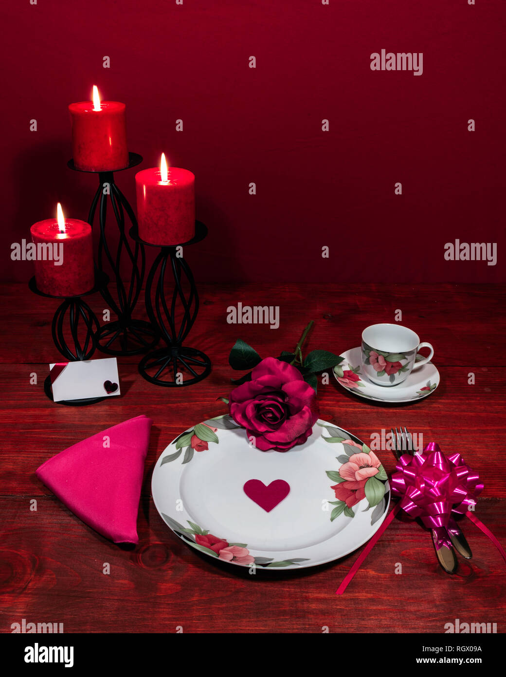 Floral pattern fine china dinnerware with matching plate, cup and saucer. pink rose, pink napkin, silverware, red candles and card Stock Photo