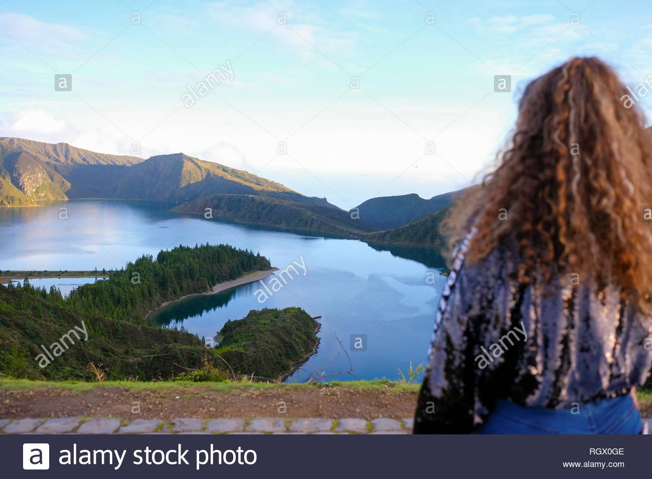 Young woman standing on top of a mountain overlooking Lagoa do Fogo in Sao Miguel, Azores, Portugal - Stock Image