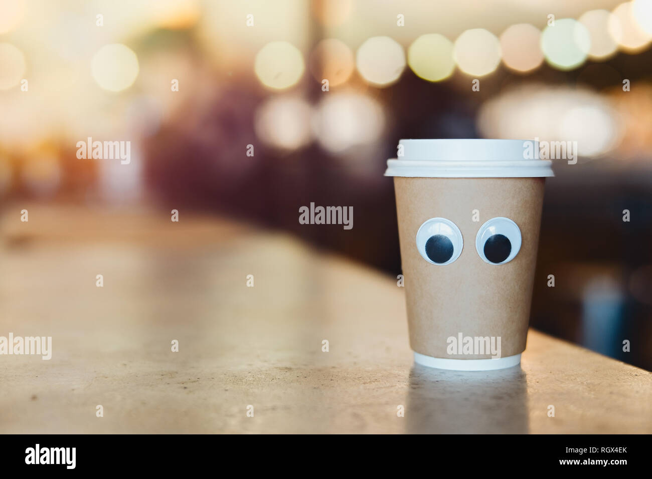 Coffee takeaway cup with cartoon eyes in cafe. Concept of hospitable cafe and good service. Cute and nice character. Stock Photo