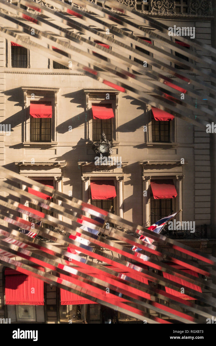 Cartier Mansion on Fifth Avenue is seen through the Diagonally-rippled glass window of the Nike Flagship store, New York City, USA - Stock Image