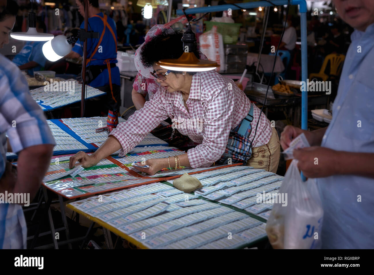 Thailand lottery. People buying lottery tickets from a female lottery ticket vendor. Southeast Asia - Stock Image
