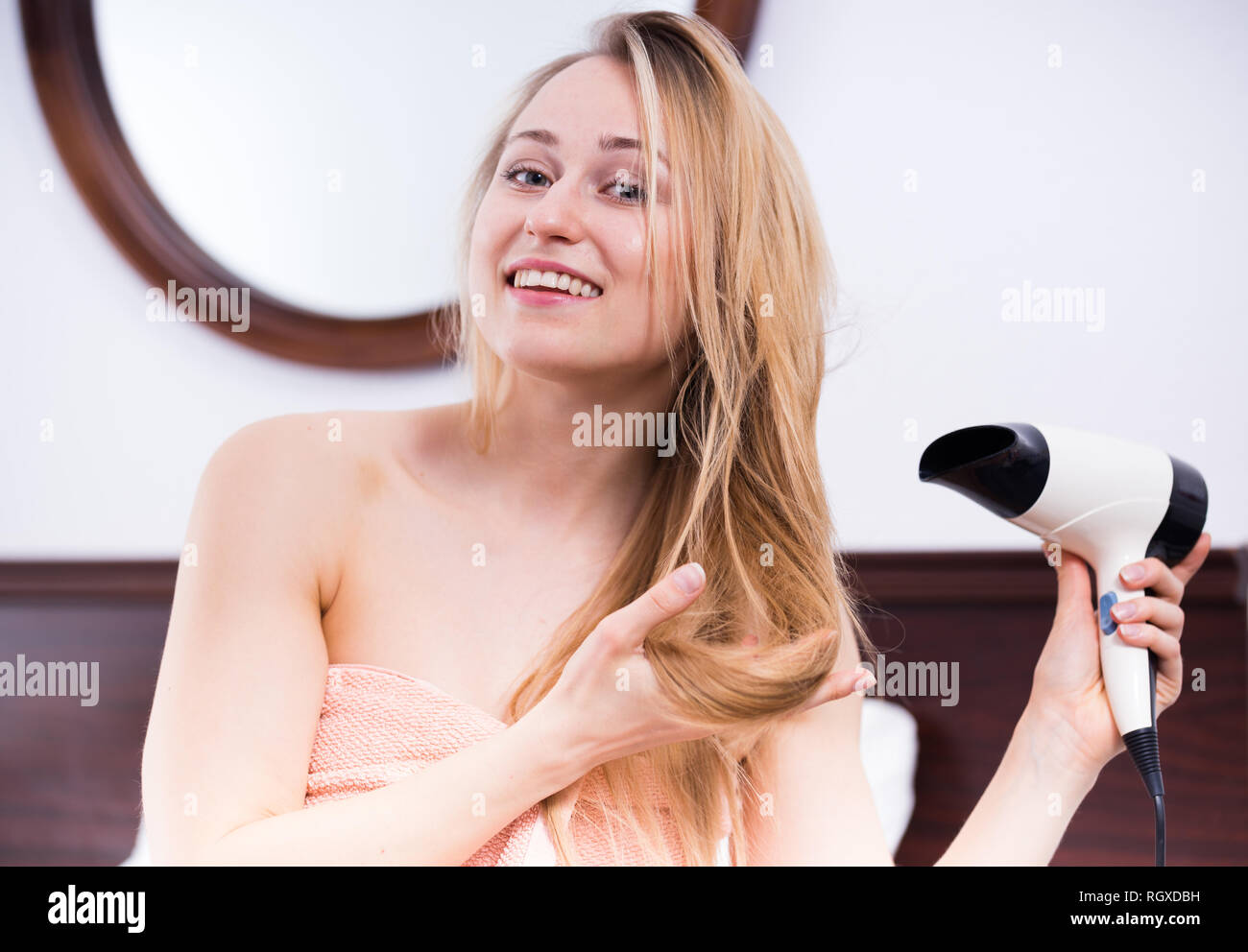 cheerful young woman using hairdryer to style her hair after shower - Stock  Image 61e81bb97