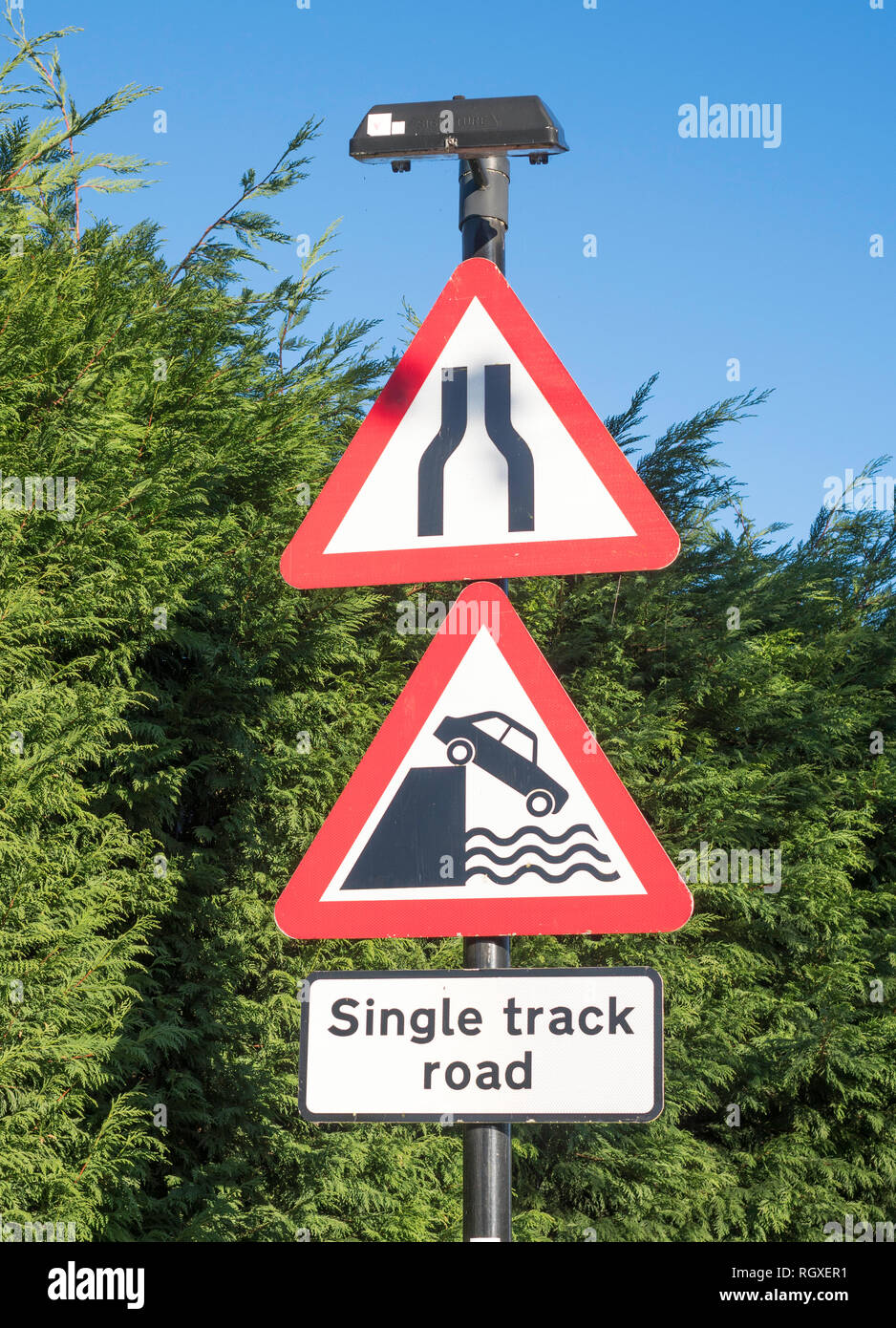 Triangular warning road signs, road narrows and river bank or quayside, a risk of drowning, England, UK - Stock Image