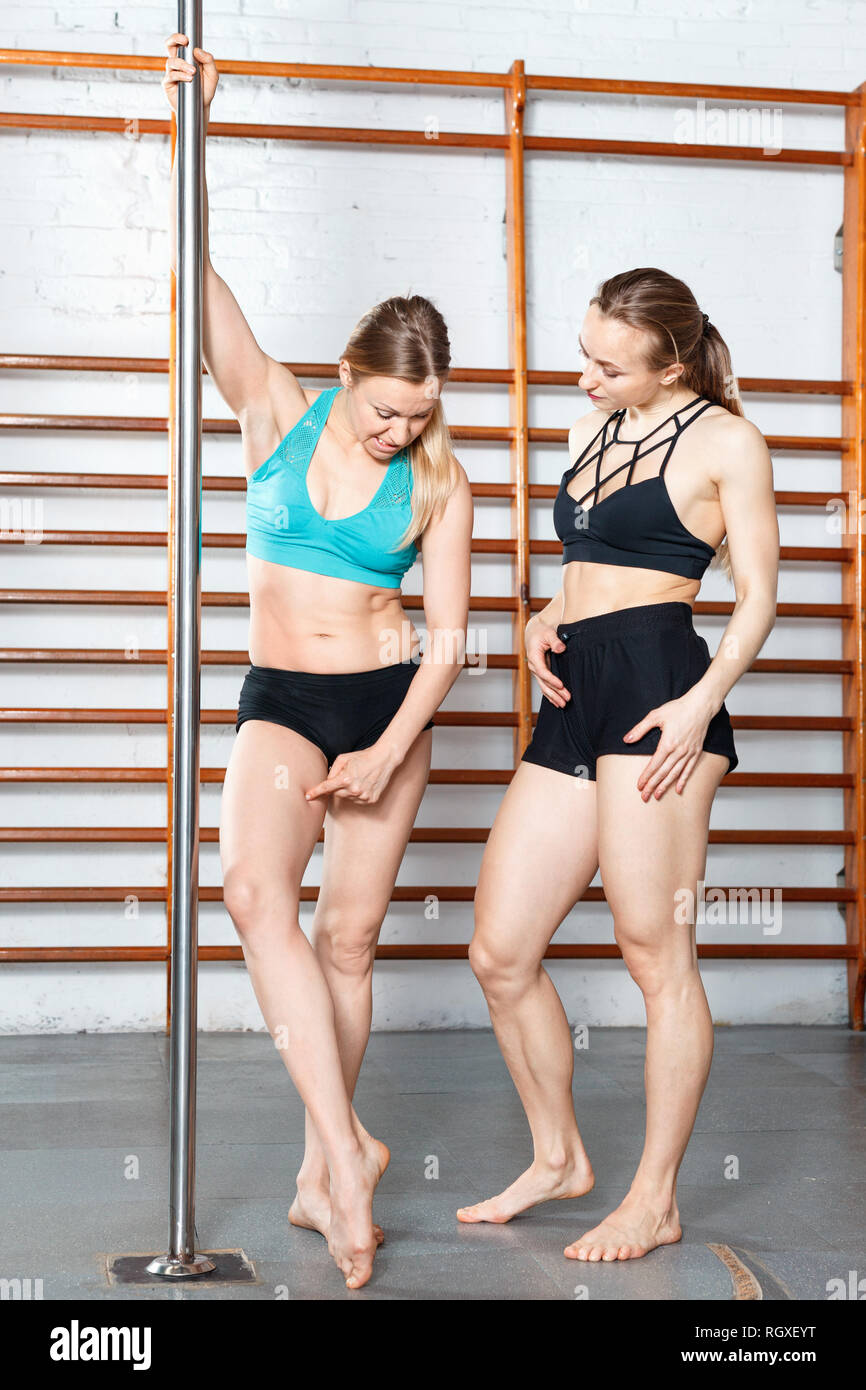 Two glad cheerful positive smiling slim girls discussing their bodies during training in fitness gym Stock Photo