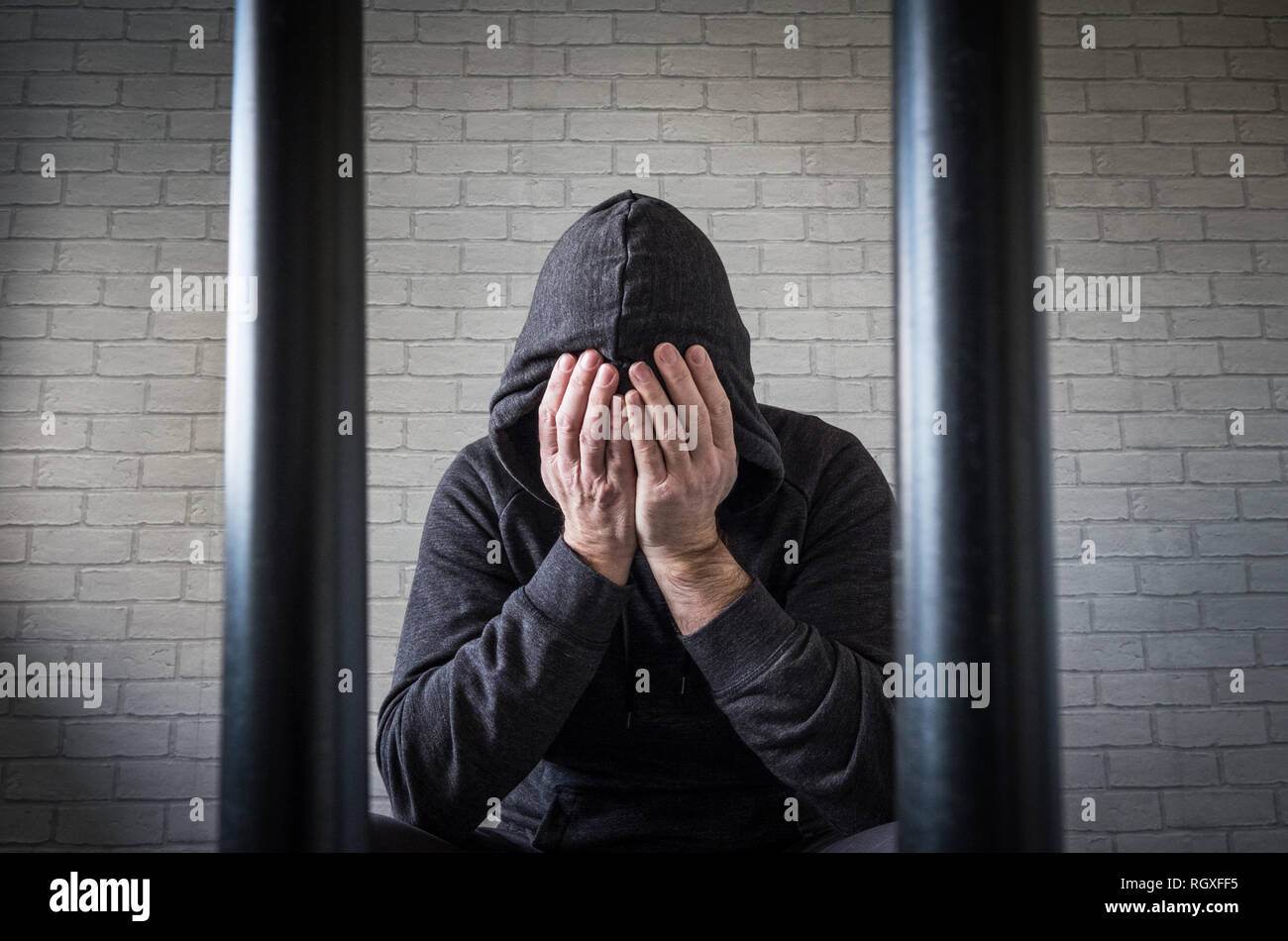 A prisoner with his head in his hands behind bars in a prison cell (picture posed by model) - Stock Image