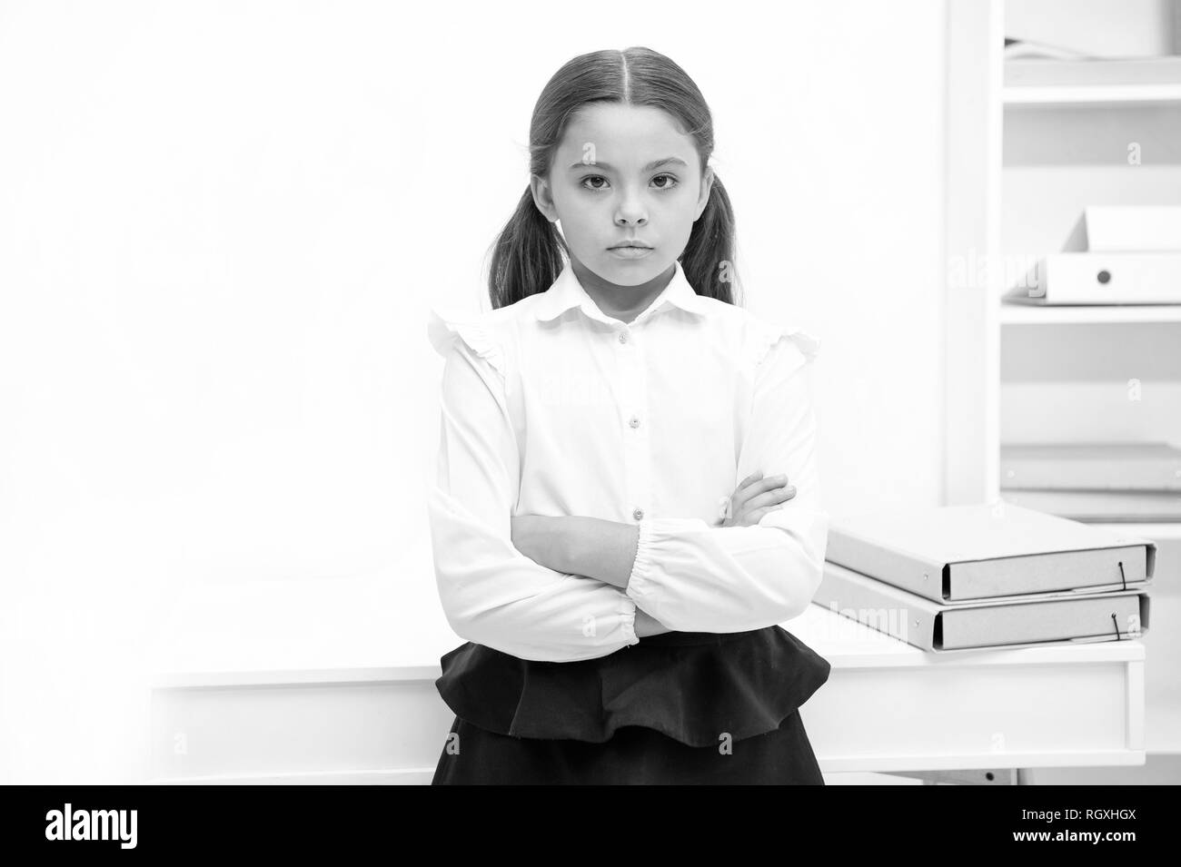 Smart glance. Child girl wears school uniform standing with crossed arms on chest. Schoolgirl smart child looks serious white interior background. Girl serious about knowledge and education in school. - Stock Image