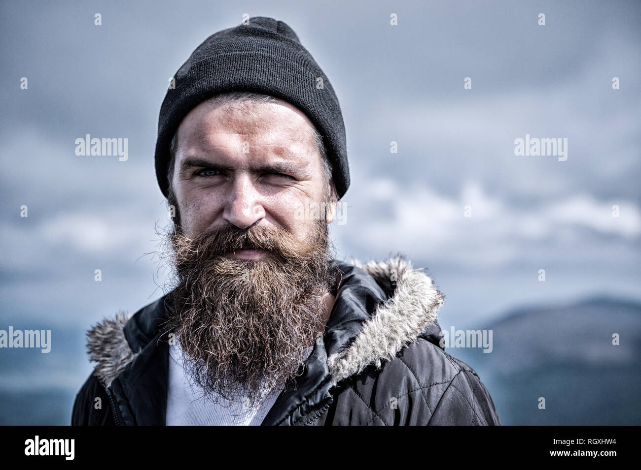 Man with long beard and mustache wears hat. Hipster on strict face with beard looks brutally while hiking. Masculinity concept. Man with brutal bearded appearance, brutal unshaven man looks untidy. - Stock Image