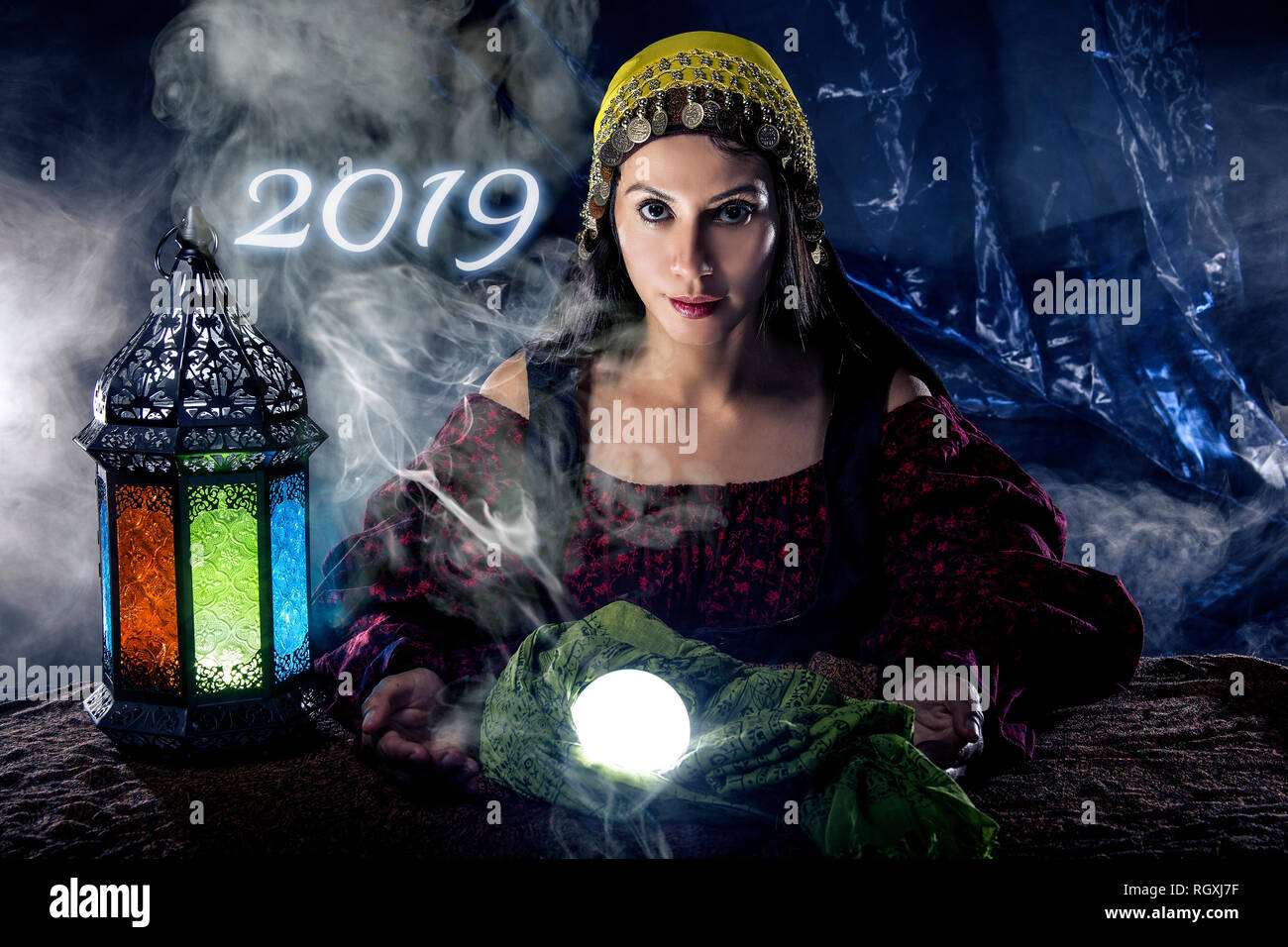 Female fortune teller or psychic reading with a cystal ball predicting the future of the year 2019 - Stock Image