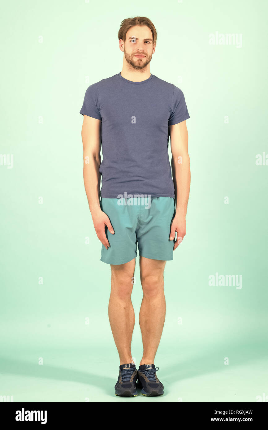 Sportsman stand arms at side. Fashion athlete in blue sport uniform. Bearded man with stylish hair. Sport fashion and style. - Stock Image