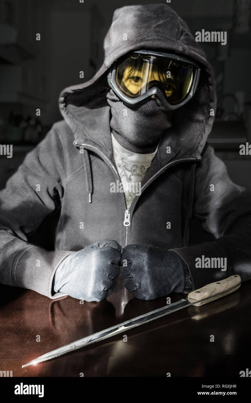 Hood and ski goggles, a young rioter or terrorist getting ready to act, fists gloved and clenched behind the long knife. Stock Photo