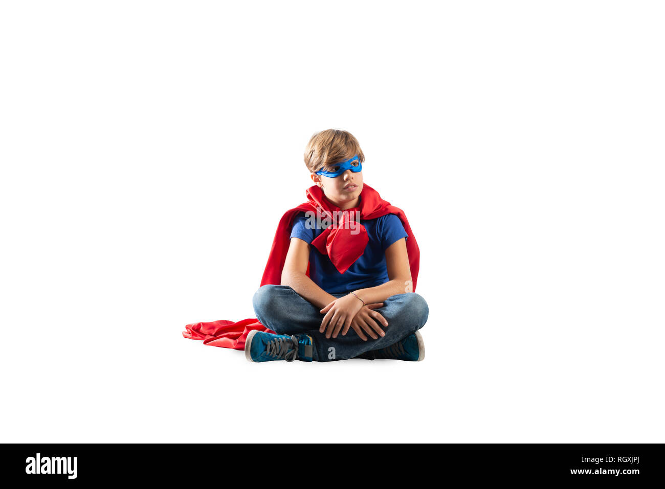 Superhero kid sitting on a wall that dreams. Isolated on white background - Stock Image
