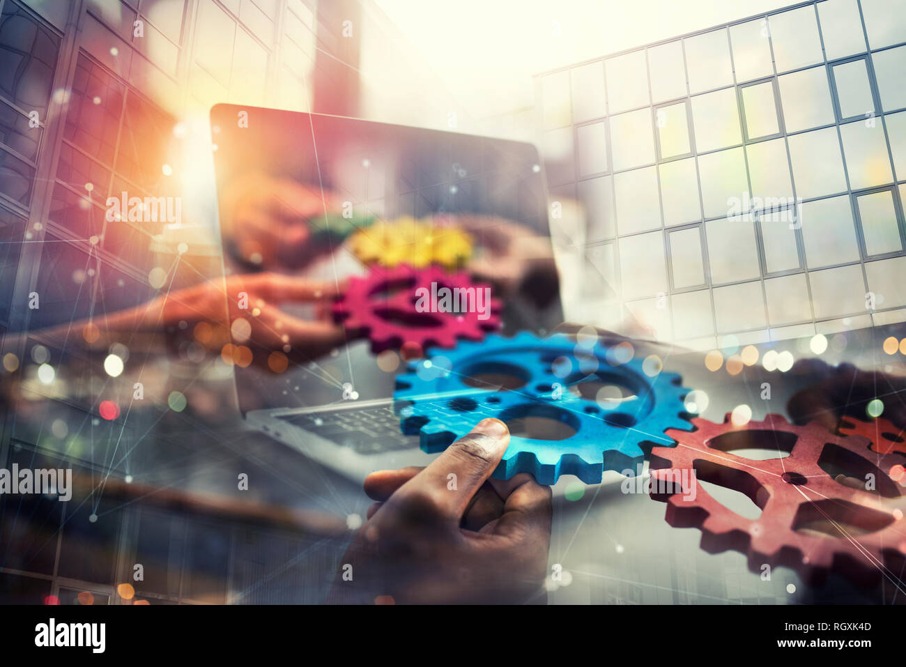 Business people with gears in hand that exit from a laptop. concept of remote cooperation and teamwork. Double exposure Stock Photo
