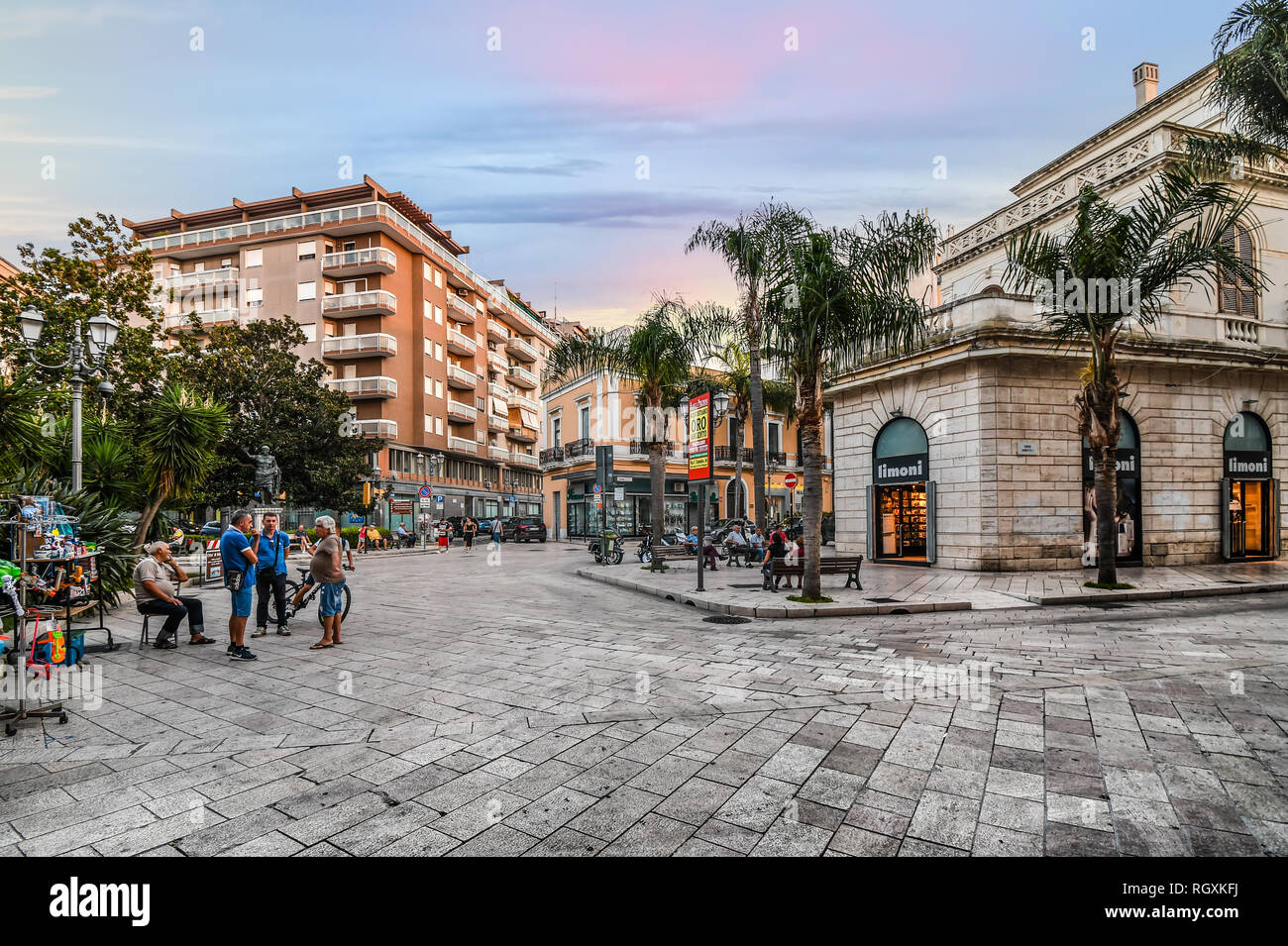 Brindisi, Italy - September 13 2018: Shops line the main street, Corso Umberto, as a group of older Italian men interact on the street. - Stock Image