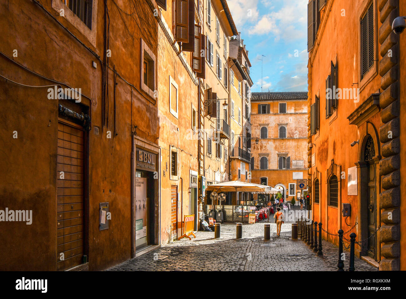 Rome, Italy - September 30 2018: A woman walks through an empty alley towards a sidewalk cafe and small piazza in the historic center of Rome, Italy Stock Photo