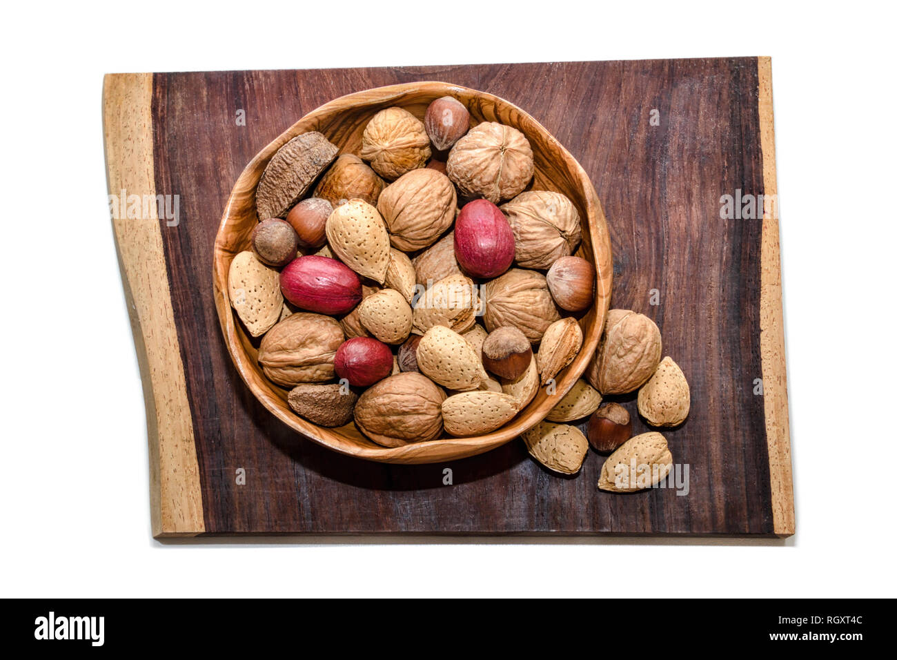 Mixed nuts in wooden bowl on piece of exotic Cola Bola wood - Stock Image