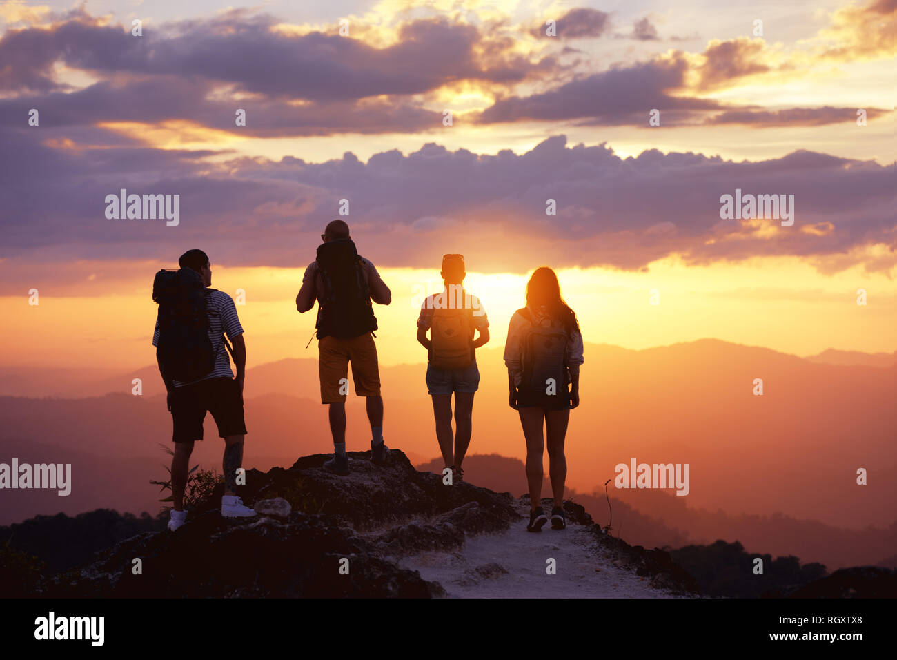 Group of four tourists or friends stands on mountain top and looks at sunset. Peoples travel concept Stock Photo