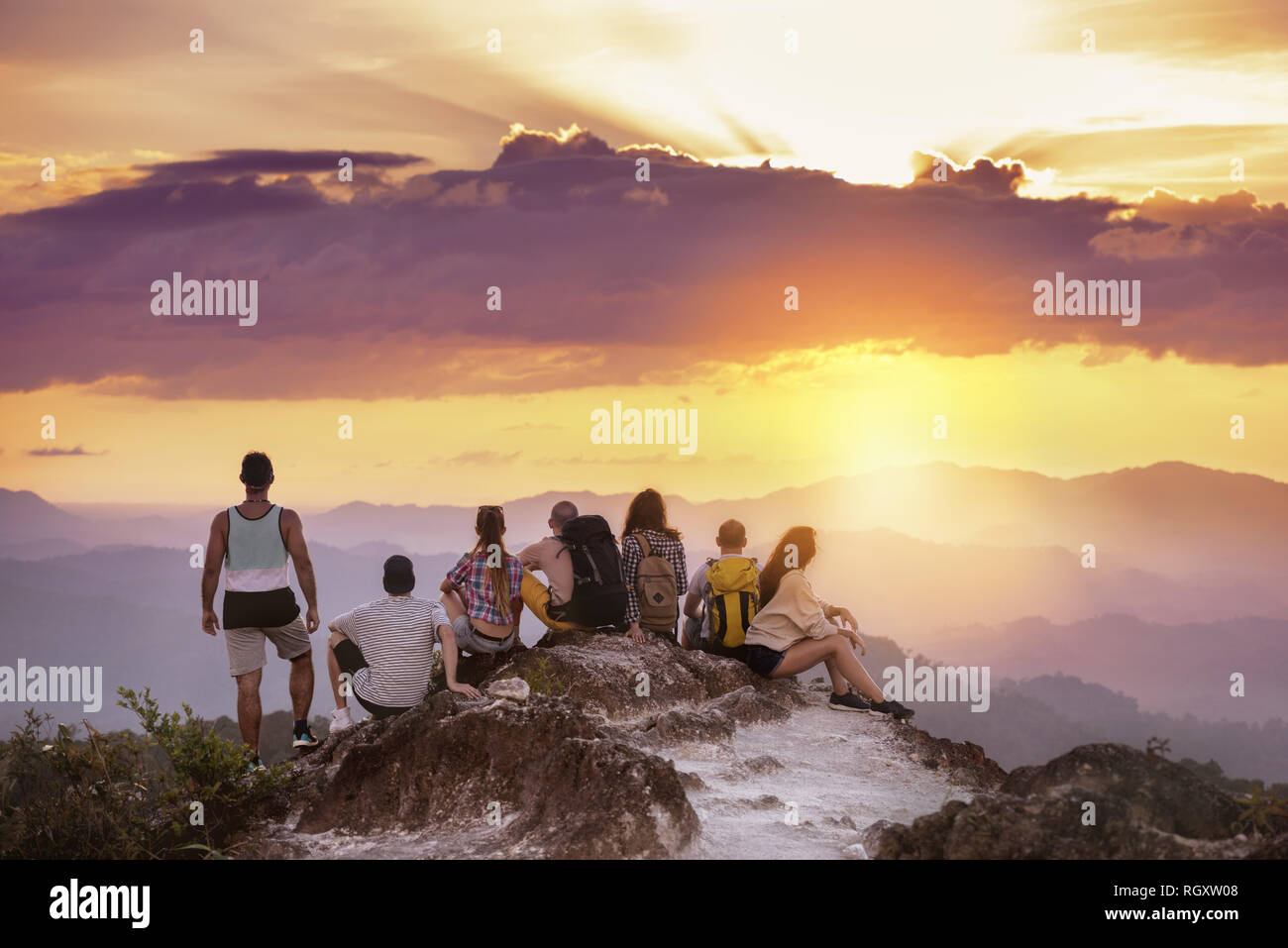 Big group of friends stands on mountain top and looks at beautiful sunset. Travel with friends concept Stock Photo