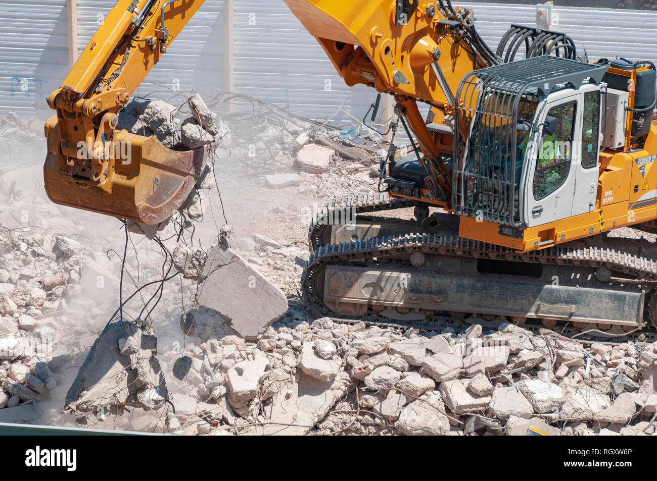 Demolition site. An excavator equipped with a bucket, evacuates reinforced concrete rubble. - Stock Image