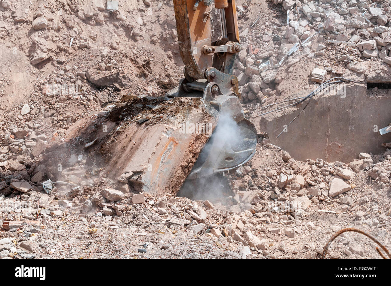 On a demolition site the bucket of an excavator pulls a