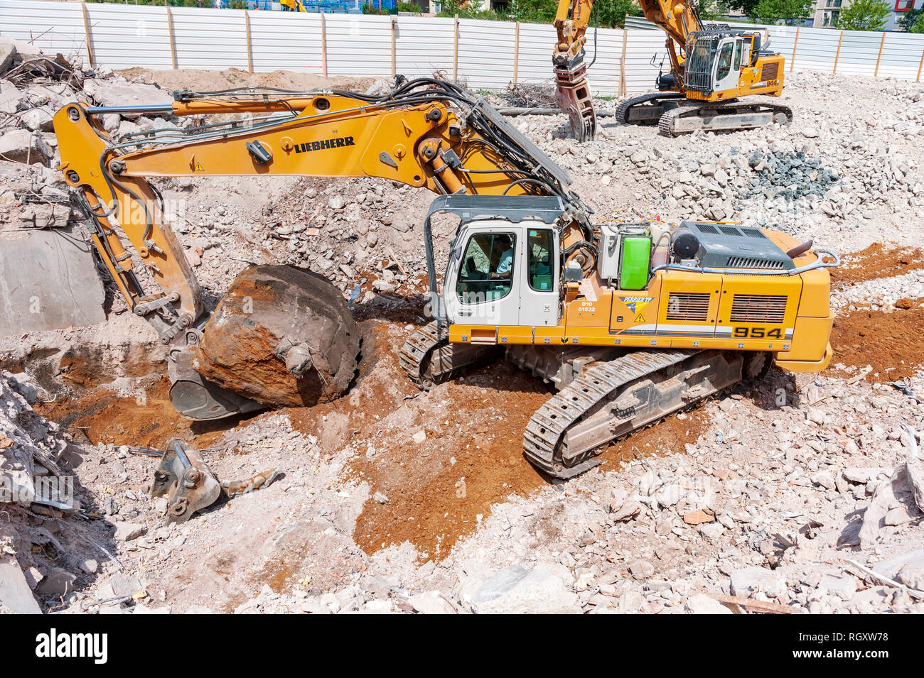 Deconstruction site. A Liebherr 954 excavator, with a bucket , extracts a large block of concrete leftover from the foundations of a building. - Stock Image
