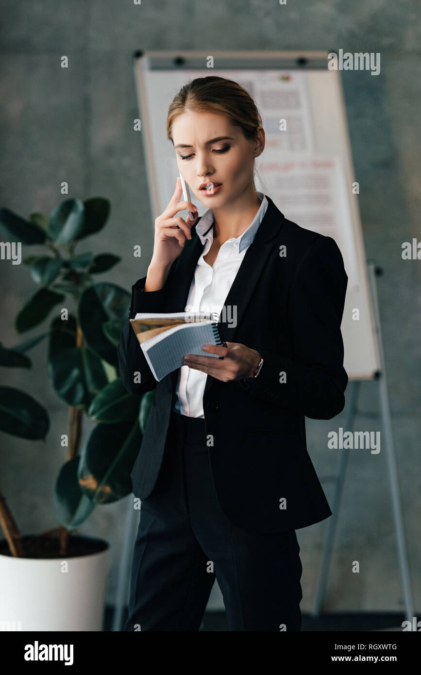Young businesswoman seriously talking on smartphone while holding notebooks in hands Stock Photo