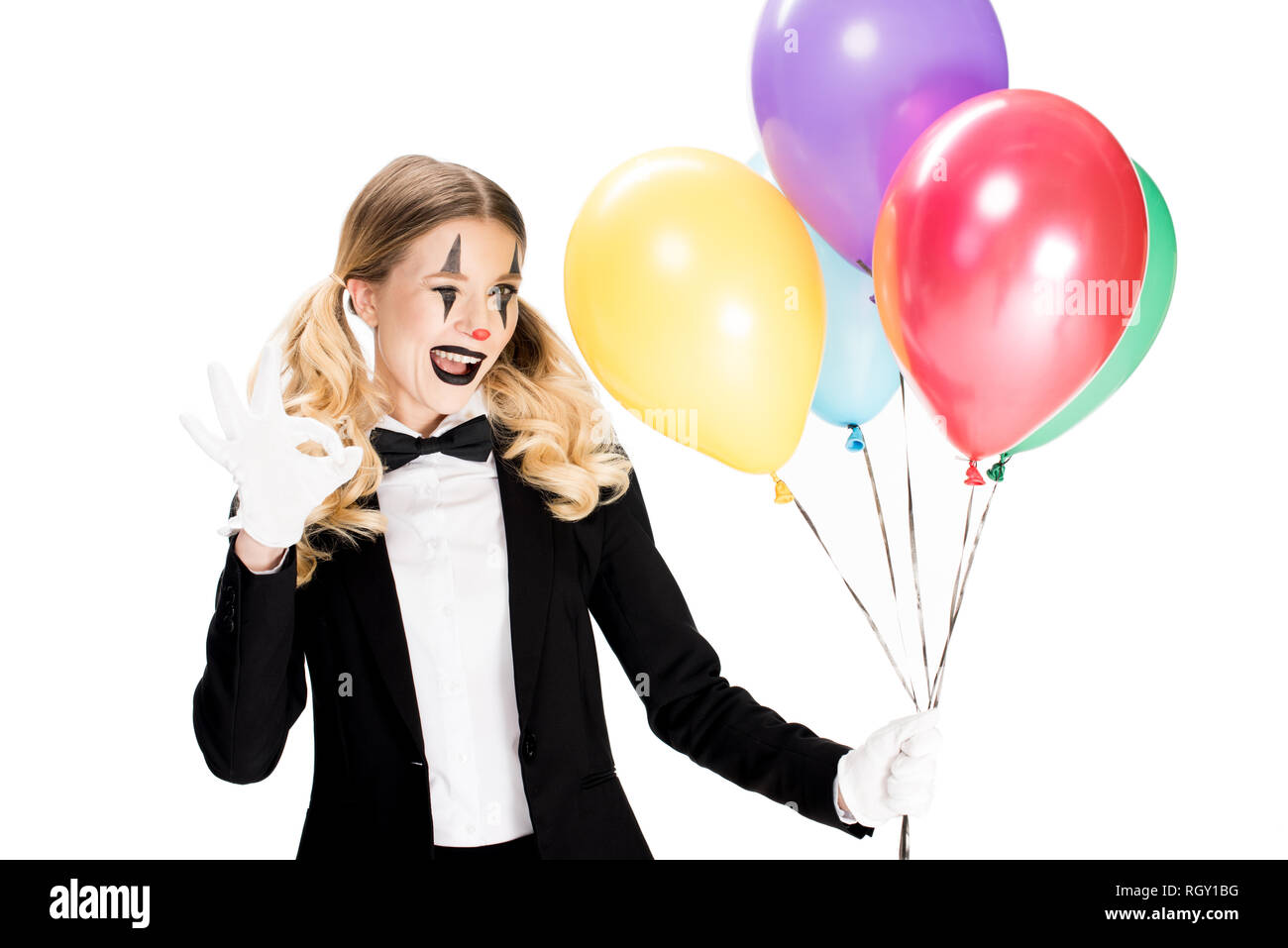 happy female clown in suit holding balloons and showing ok sign isolated on white - Stock Image