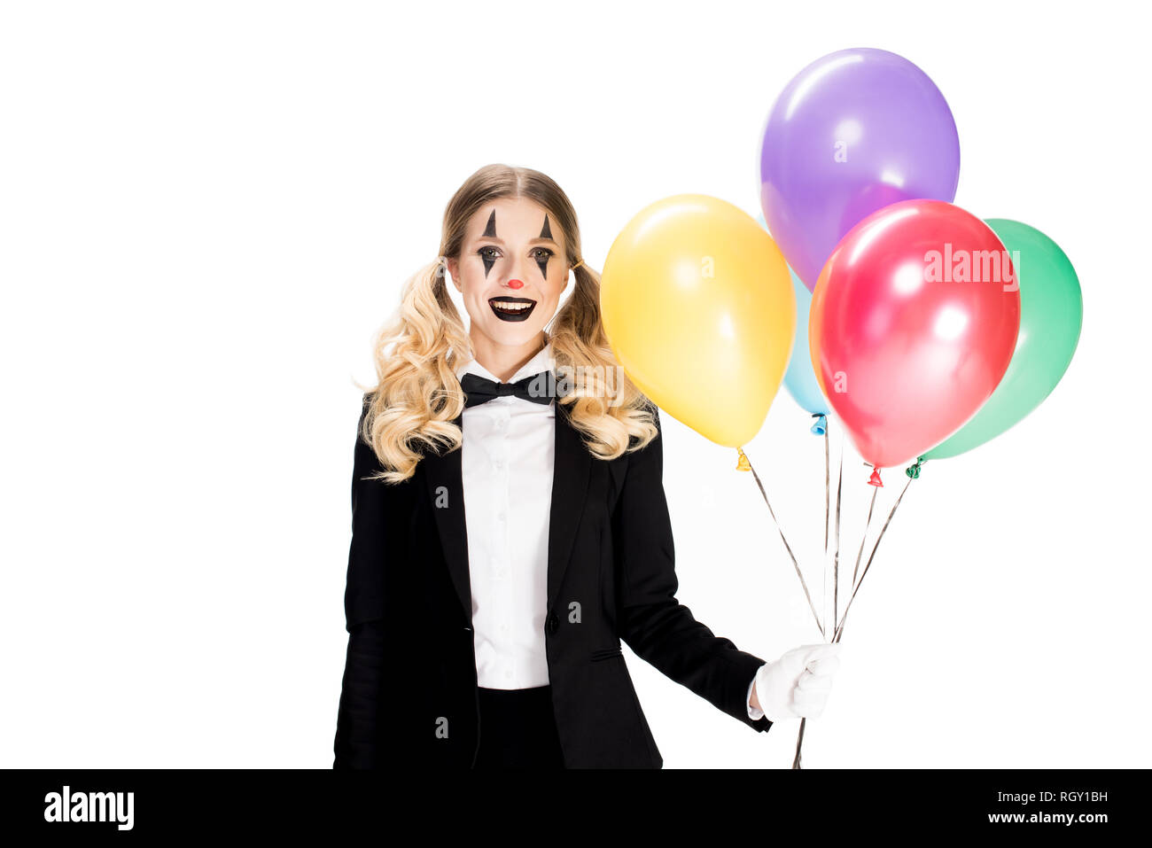cheerful female clown in suit holding balloons and smiling isolated on white - Stock Image