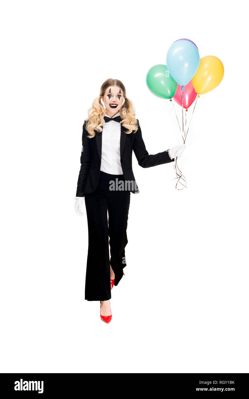 happy female clown in suit holding balloons and smiling isolated on white - Stock Image
