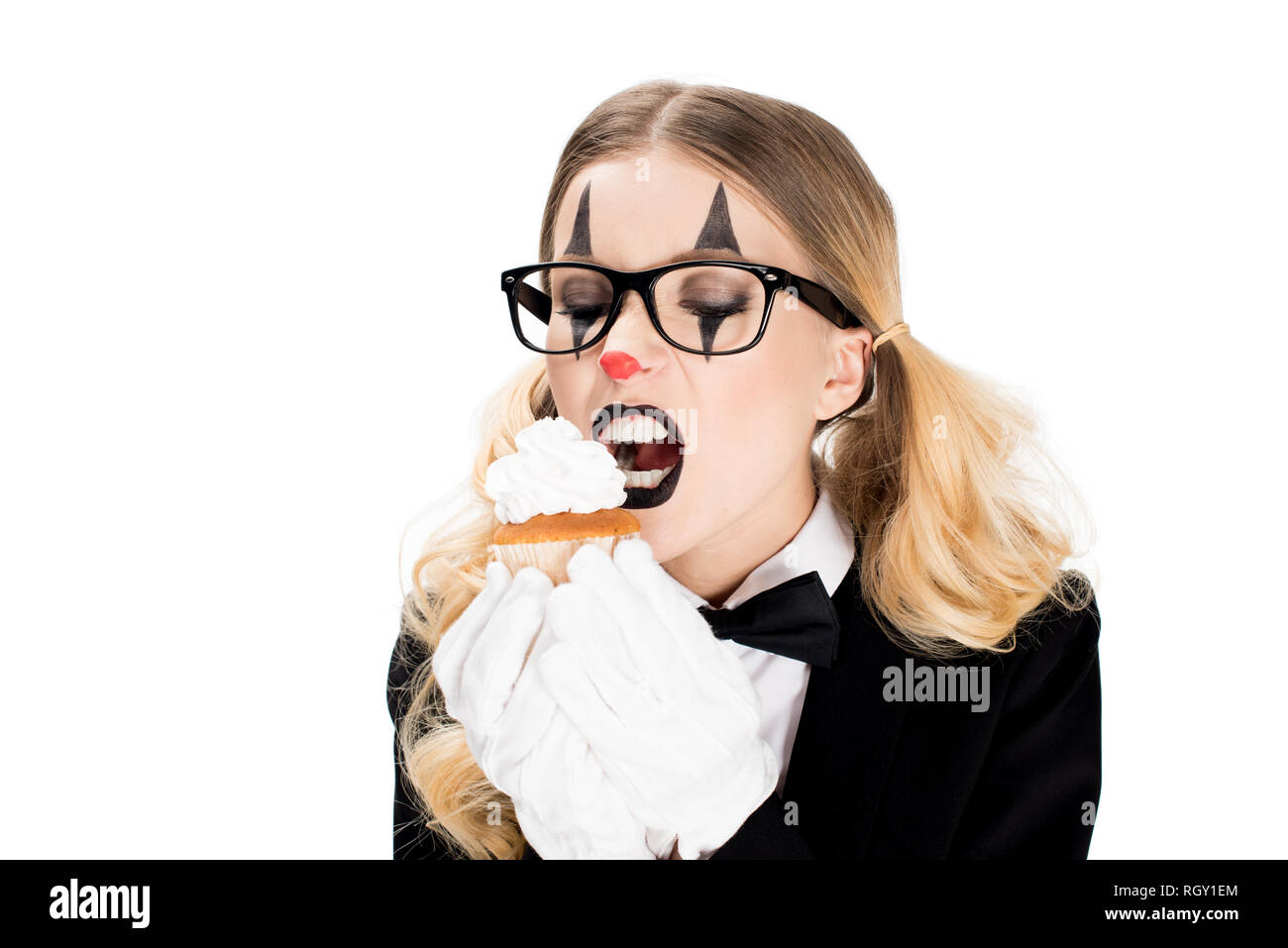 female clown in glasses looking at tasty cupcake isolated on white - Stock Image