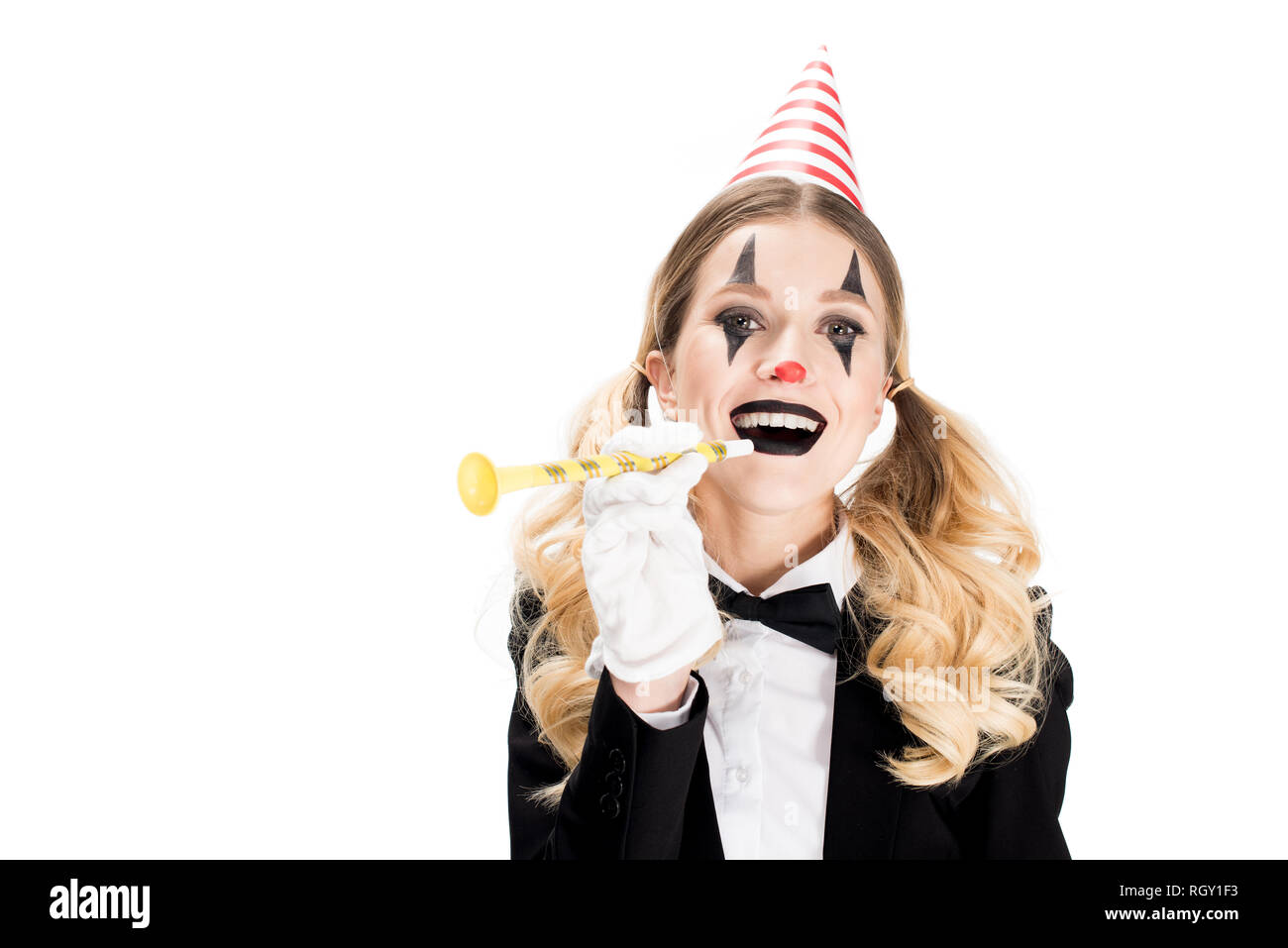 female clown in suit smiling while holding birthday blower isolated on white - Stock Image