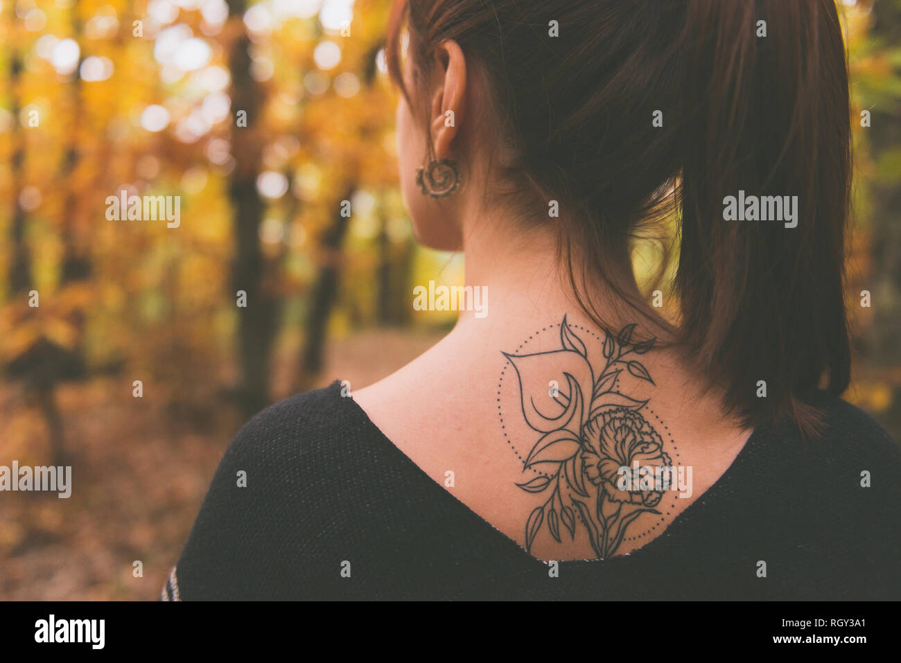 Tattoo on the back of a young girl with reddish hair dressed in a poncho in an autumnal forest - Stock Image