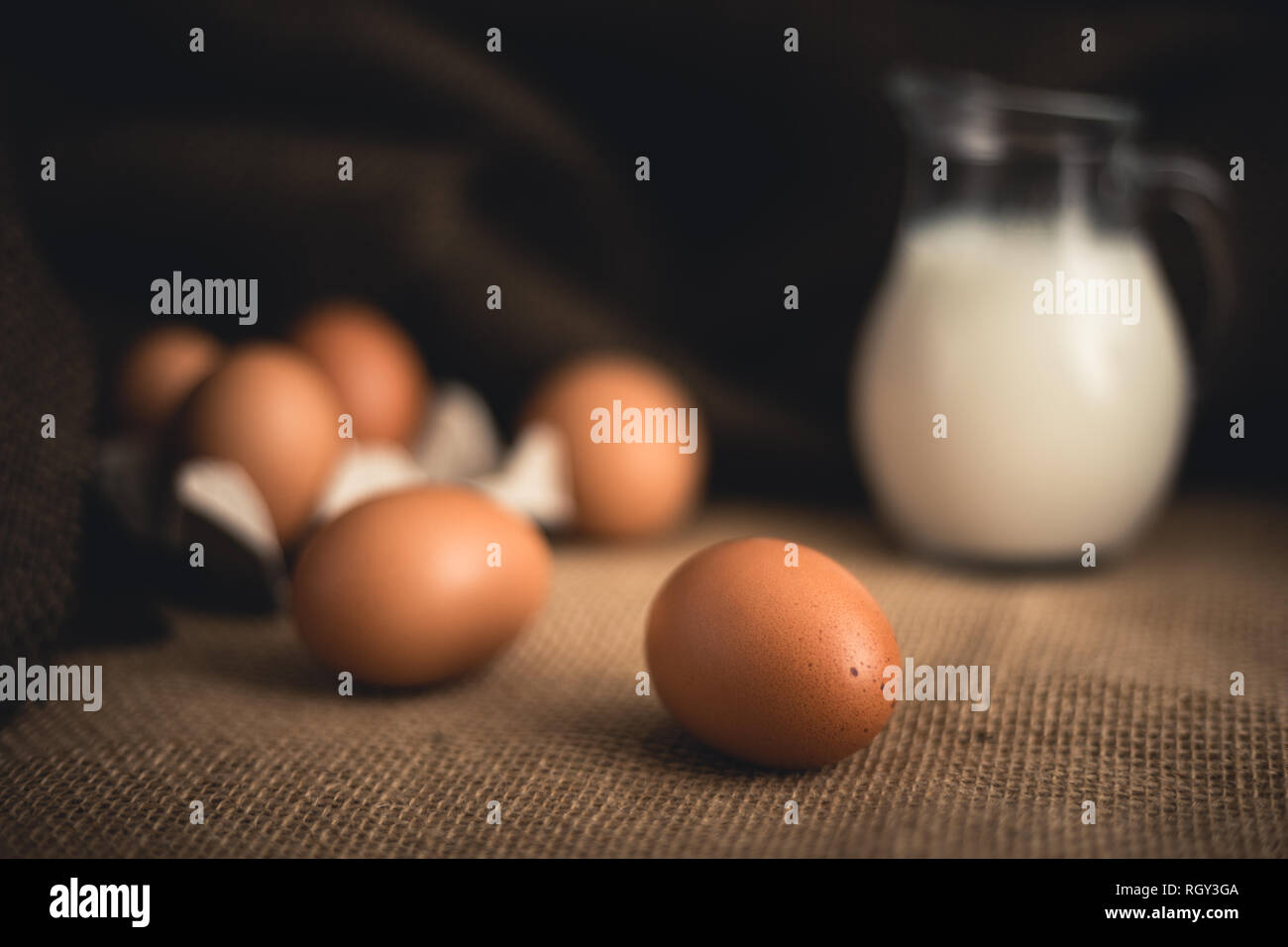 Photo of raw illuminated eggs  in kitchen with jute on dark blurry background Close-up photography of bio chicken eggs in egg box with milk in a ewer  Stock Photo