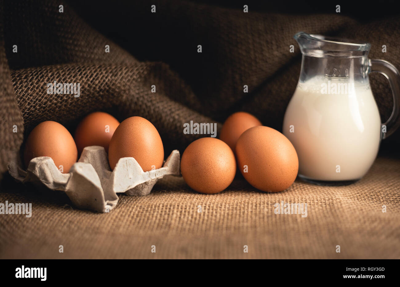 Photo of raw illuminated eggs  in kitchen with jute on dark background. Close-up photography of bio chicken eggs in egg box with milk in a ewer glass. Stock Photo