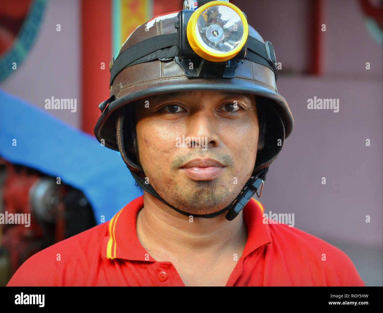 Indonesian on-call firefighter wears an improvised firefighter's helmet with attached DIY helmet lamp. - Stock Image