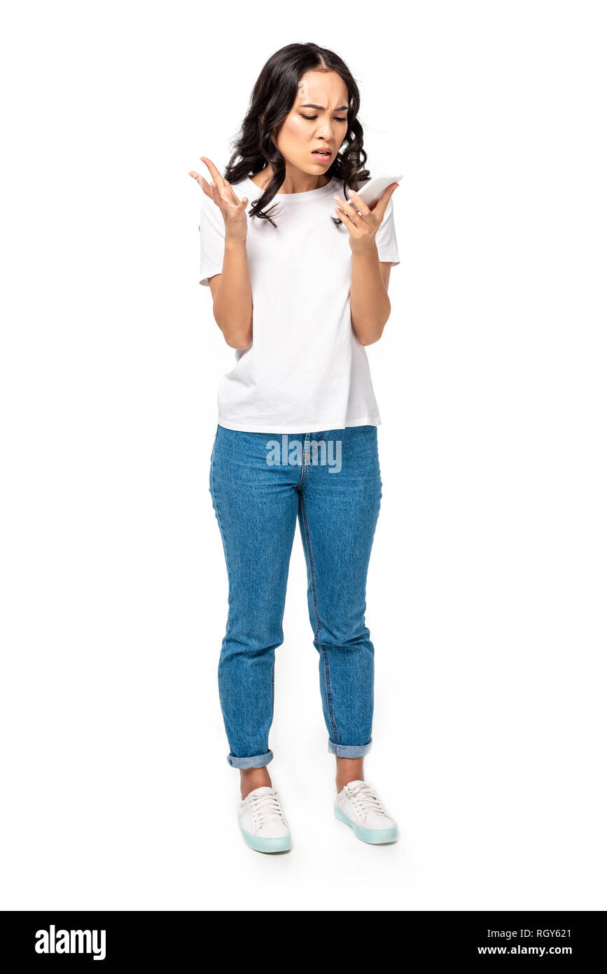 e034f5ea79 Angry asian girl in white t-shirt and blue jeans using smartphone isolated  on white