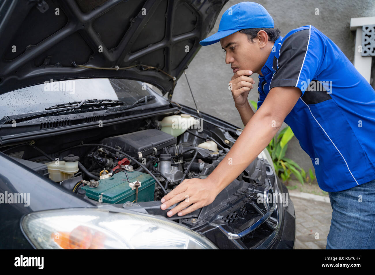 mechanic doing some inspection on car's engine  - Stock Image