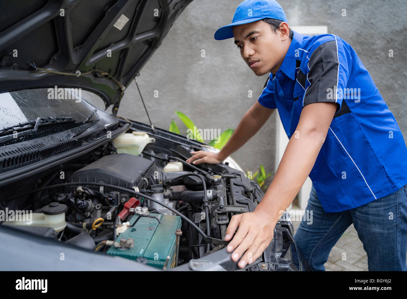 blue uniform car engineer worker looking into car's engine - Stock Image