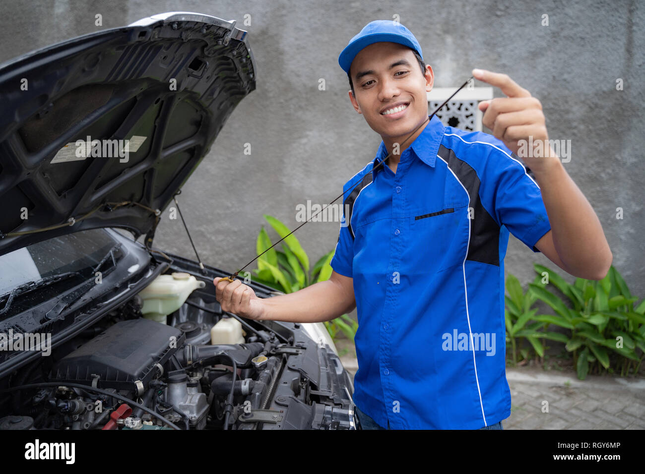 mechanic with uniform inspecting the car oil - Stock Image