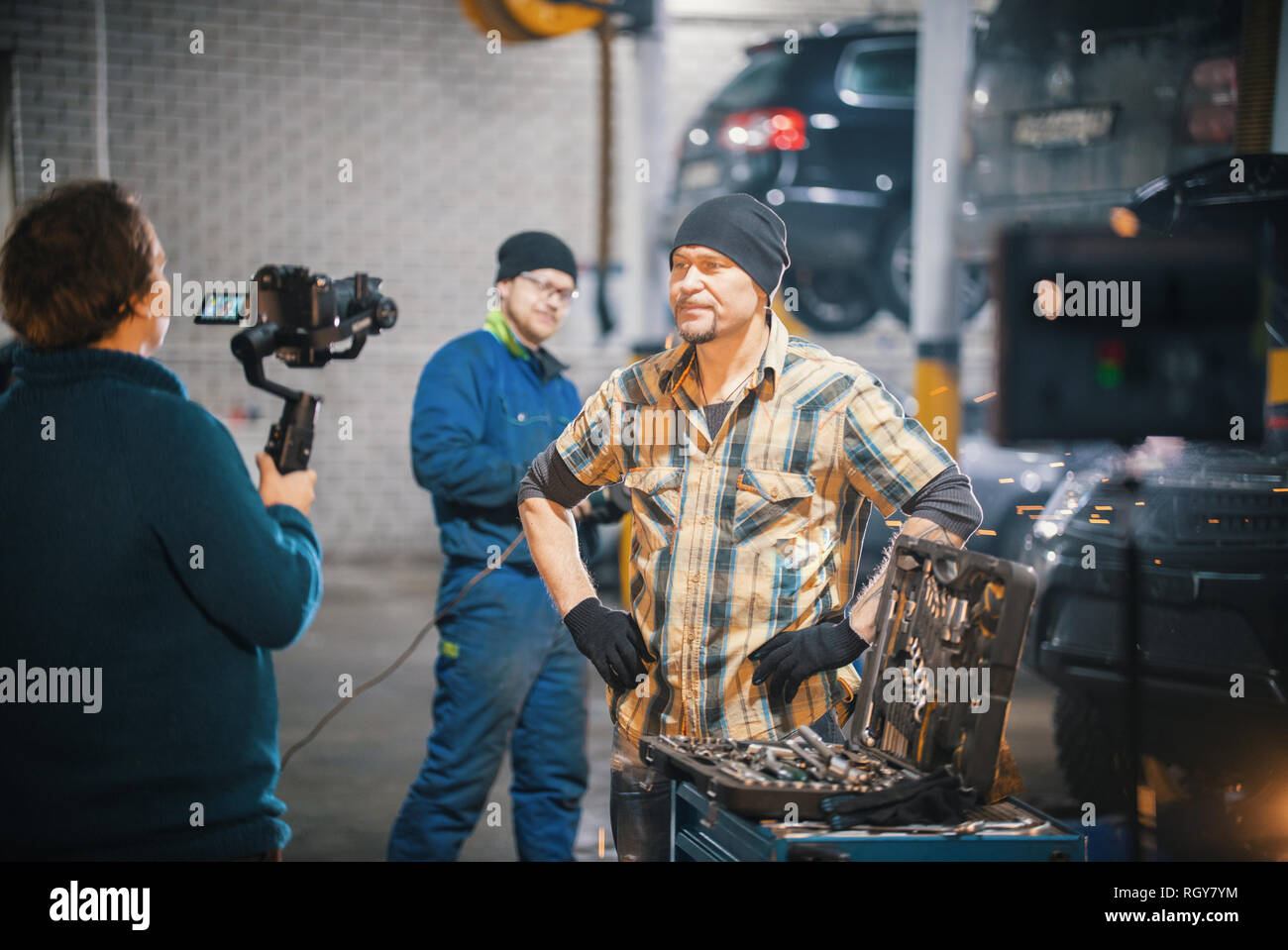 Car repair service. Backstage of shooting. Brutal mechanic man standing in front of a camera - Stock Image