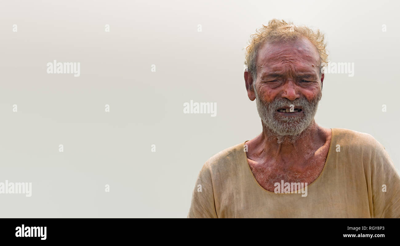 Portrait of poverty stricken Old Aged Male of SouthAsian origin in his late 70s, posing in dubious mood. - Stock Image