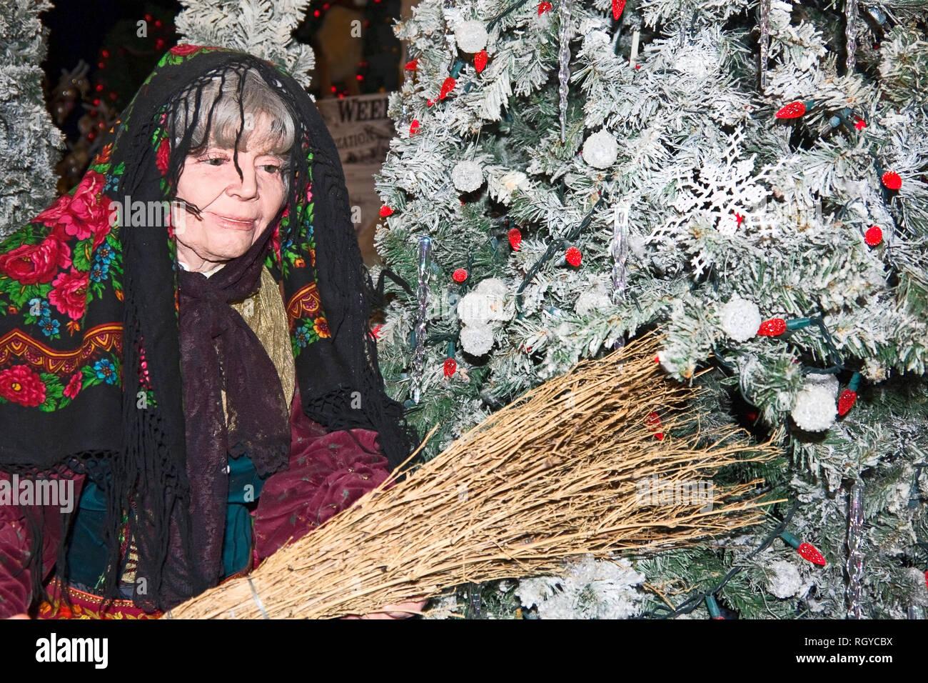 La Befana of Italy figure; twig broom; head scarf; decorated Christmas tree; holiday decoration; horizontal, PR - Stock Image